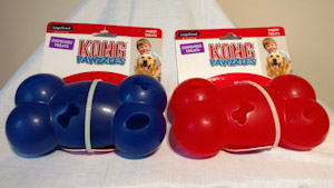 Two plastic hollow bone, blue one and a red one, with different sized holes for stuffing and dispensing treats.